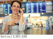 Купить «Красивая молодая женщина с багажом в зале ожидания аэропорта  разговаривает по сотовому телефону», фото № 3301339, снято 16 июля 2010 г. (c) Losevsky Pavel / Фотобанк Лори
