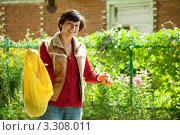 Купить «Молодая женщина-садовник удобряет почву», фото № 3308011, снято 23 августа 2011 г. (c) Яков Филимонов / Фотобанк Лори