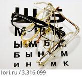 Очки, лежащие на таблице Сивцева для проверки зрения. Стоковое фото, фотограф Трошина Елена / Фотобанк Лори