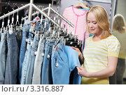 Купить «Женщина выбирает джинсы в магазине одежды», фото № 3316887, снято 23 октября 2018 г. (c) Дмитрий Калиновский / Фотобанк Лори