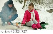 Молодая пара жарит сардельки на пикнике в зимнем лесу. Стоковое видео, видеограф Владимир Никулин / Фотобанк Лори