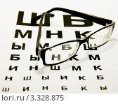 Очки, лежащие на таблице для проверки зрения. Стоковое фото, фотограф Трошина Елена / Фотобанк Лори
