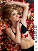 Купить «Девушка в бюстгальтере лежит в розовых лепестках», фото № 3335283, снято 29 апреля 2010 г. (c) Сергей Сухоруков / Фотобанк Лори