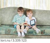 Купить «Два мальчика сидят на диване с книгами в руках», фото № 3339123, снято 9 марта 2012 г. (c) Андрей Щекалев (AndreyPS) / Фотобанк Лори