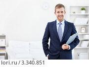 Купить «Успешный молодой мужчина в строгом костюме держит планшет в руке и стоит в квартире», фото № 3340851, снято 6 октября 2011 г. (c) Raev Denis / Фотобанк Лори