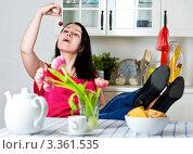 Молодая женщина ест вишню, забросив ноги на стол. Стоковое фото, фотограф Darkbird77 / Фотобанк Лори