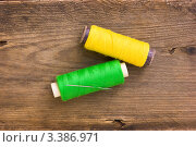Купить «Жёлтые и зелёные нитки в катушках на деревянной доске», фото № 3386971, снято 3 февраля 2011 г. (c) Олег Жуков / Фотобанк Лори