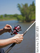 Купить «Катушка для рыбной ловли на удочке в мужских руках», фото № 3387831, снято 2 июня 2011 г. (c) Олег Жуков / Фотобанк Лори