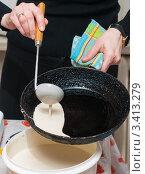 Купить «Масленица.Женщина заливает тесто  на сковородку для жарки блинов», эксклюзивное фото № 3413279, снято 25 февраля 2012 г. (c) Игорь Низов / Фотобанк Лори