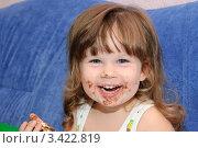 Маленькая смеющаяся девочка ест шоколадное печенье, фото № 3422819, снято 28 февраля 2017 г. (c) Сергей Галушко / Фотобанк Лори