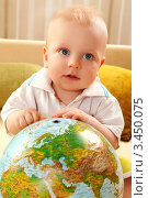 Маленький мальчик с глобусом сидит на диване. Стоковое фото, фотограф Емельянова Карина / Фотобанк Лори