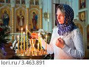 Девушка ставит свечку в православном храме (2012 год). Редакционное фото, фотограф Андрей Ярославцев / Фотобанк Лори