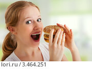 Купить «Блондинка с гамбургером в руках», фото № 3464251, снято 1 марта 2012 г. (c) Евгений Атаманенко / Фотобанк Лори