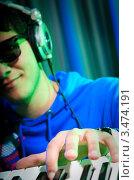Купить «Молодой парень в очках и наушниках играет на синтезаторе», фото № 3474191, снято 11 февраля 2012 г. (c) Elnur / Фотобанк Лори