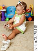 Маленькая девочка надевает сандалии (2010 год). Редакционное фото, фотограф Емельянова Карина / Фотобанк Лори