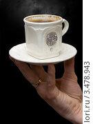 Мужская рука держит белую фарфоровую чашку с кофе на черном фоне. Стоковое фото, фотограф юлия юрочка / Фотобанк Лори