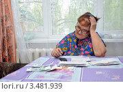 Купить «Пенсионерка подсчитывает сумму по квитанции за услуги ЖКХ, сидя за столом дома», фото № 3481939, снято 1 мая 2012 г. (c) Мастепанов Павел / Фотобанк Лори