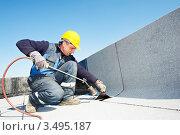 Купить «Рабочий покрывает крышу кровельным войлоком», фото № 3495187, снято 11 апреля 2012 г. (c) Дмитрий Калиновский / Фотобанк Лори