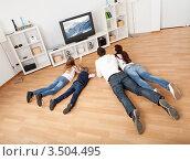 Купить «Члены семьи лежат на животах перед телевизором», фото № 3504495, снято 16 октября 2011 г. (c) Андрей Попов / Фотобанк Лори