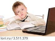 Уставший мальчик сидит пере раскрытой книгой и ноутбуком. Ученик. Стоковое фото, фотограф Юрий Соловьёв / Фотобанк Лори