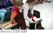 Купить «Мама помогает дочке примерить коньки в магазине», видеоролик № 3531039, снято 25 декабря 2008 г. (c) Losevsky Pavel / Фотобанк Лори