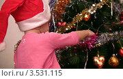 Купить «Девочка в колпаке Санты-Клауса вешает елочный шар на елку», видеоролик № 3531115, снято 28 декабря 2008 г. (c) Losevsky Pavel / Фотобанк Лори