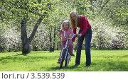 Купить «Мама учит дочку кататься на велосипеде в парке», видеоролик № 3539539, снято 26 мая 2009 г. (c) Losevsky Pavel / Фотобанк Лори