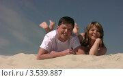Купить «Пара болтает ногами лежа на песке», видеоролик № 3539887, снято 29 июня 2009 г. (c) Losevsky Pavel / Фотобанк Лори