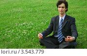 Купить «Мужчина  в костюме сидит на траве в позе лотоса», видеоролик № 3543779, снято 22 октября 2009 г. (c) Losevsky Pavel / Фотобанк Лори