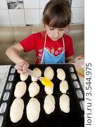 Купить «Маленькая девочка смазывает пирожки взбитым яйцом», фото № 3544975, снято 24 мая 2012 г. (c) Ольга Денисова / Фотобанк Лори