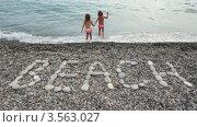 """Купить «Две девочки на пляже входят в морскую воду на фоне надписи из гальки """"Пляж""""», видеоролик № 3563027, снято 22 января 2010 г. (c) Losevsky Pavel / Фотобанк Лори"""