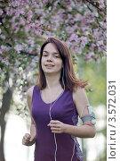Девушка бежит по цветущему парку и слушает музыку. Стоковое фото, фотограф Юрий Викулин / Фотобанк Лори