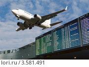 Купить «Летящий самолёт и табло аэропорта», фото № 3581491, снято 2 октября 2011 г. (c) Mikhail Starodubov / Фотобанк Лори