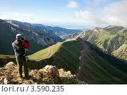 Купить «Турист фотографирует вид на ущелье с извилистой дорогой в горах Тянь-Шаня», фото № 3590235, снято 3 июня 2012 г. (c) Николай Винокуров / Фотобанк Лори