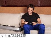 Купить «Музыкант работает над текстом песни сидя на диване», фото № 3624335, снято 27 мая 2012 г. (c) Игорь Долгов / Фотобанк Лори