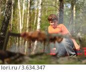 Купить «Мальчик в оранжевой футболке сидит возле костра, на котором готовится шашлык», фото № 3634347, снято 7 мая 2011 г. (c) Losevsky Pavel / Фотобанк Лори