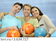 Купить «Двое молодых мужчин и девушка стоят обнявшись на голубом фоне. Все трое держат в руках шары для игры в боулинг», фото № 3634727, снято 21 июня 2011 г. (c) Losevsky Pavel / Фотобанк Лори