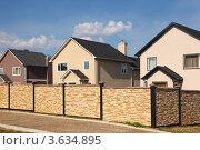 Купить «Современные двухэтажные коттеджи за декоративным каменным забором», фото № 3634895, снято 14 августа 2010 г. (c) Losevsky Pavel / Фотобанк Лори