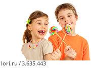Купить «Счастливые брат и сестра с леденцами, белый фон», фото № 3635443, снято 1 апреля 2011 г. (c) Losevsky Pavel / Фотобанк Лори