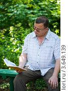Купить «Мужчина сидит на лавочке в парке и читает  книгу», фото № 3649139, снято 18 июня 2012 г. (c) Валерия Потапова / Фотобанк Лори