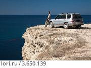 Купить «Мужчина отдыхает возле автомобиля на краю скалы у моря», фото № 3650139, снято 26 сентября 2011 г. (c) SummeRain / Фотобанк Лори