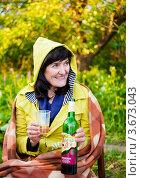 Купить «Счастливая женщина закуталась в одеяло на улице сидя на стуле с бутылкой вина и стаканом», эксклюзивное фото № 3673043, снято 3 июня 2012 г. (c) Игорь Низов / Фотобанк Лори