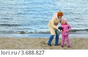 Купить «Мама кружит дочку на берегу реки осенним днем», видеоролик № 3688827, снято 9 марта 2010 г. (c) Losevsky Pavel / Фотобанк Лори