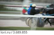 Купить «Жокеи в упряжке с лошадьми на скачках на ипподроме», видеоролик № 3689855, снято 30 марта 2010 г. (c) Losevsky Pavel / Фотобанк Лори