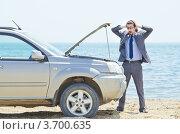 Бизнесмен в ужасе смотрит в открытый капот автомобиля на пляже. Стоковое фото, фотограф Elnur / Фотобанк Лори
