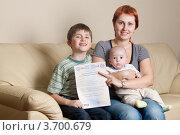 Молодая женщина с двумя детьми держит в руках сертификат на материнский капитал (2012 год). Редакционное фото, фотограф Максим Стриганов / Фотобанк Лори