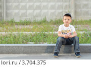 Мальчик сидит на бордюре у дороги (2012 год). Редакционное фото, фотограф Денис Омельченко / Фотобанк Лори