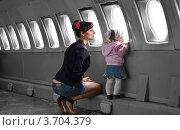 Мама с дочерью летят в самолете и смотрят в иллюминатор. Стоковое фото, фотограф Денис Омельченко / Фотобанк Лори