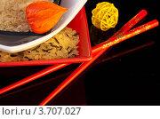 Рис в разноцветных тарелках, физалис, палочки для еды и желтый плетеный шар на черном фоне. Стоковое фото, фотограф Лариса Кривошапка / Фотобанк Лори