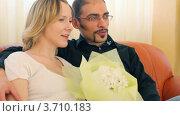 Купить «Мужчина и женщина сидят на диване с букетом цветов», видеоролик № 3710183, снято 7 декабря 2010 г. (c) Losevsky Pavel / Фотобанк Лори